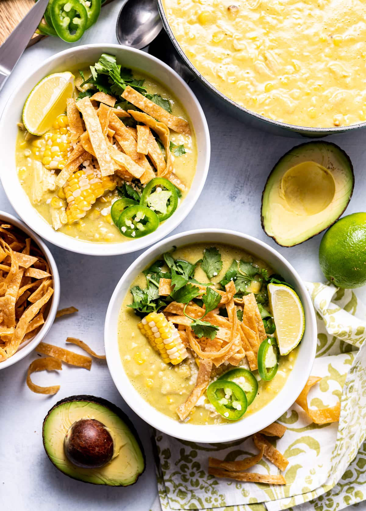 white bowls of green yellow chicken avocado chowder with corn tortilla strips limes jalapeno slices and avocado halves