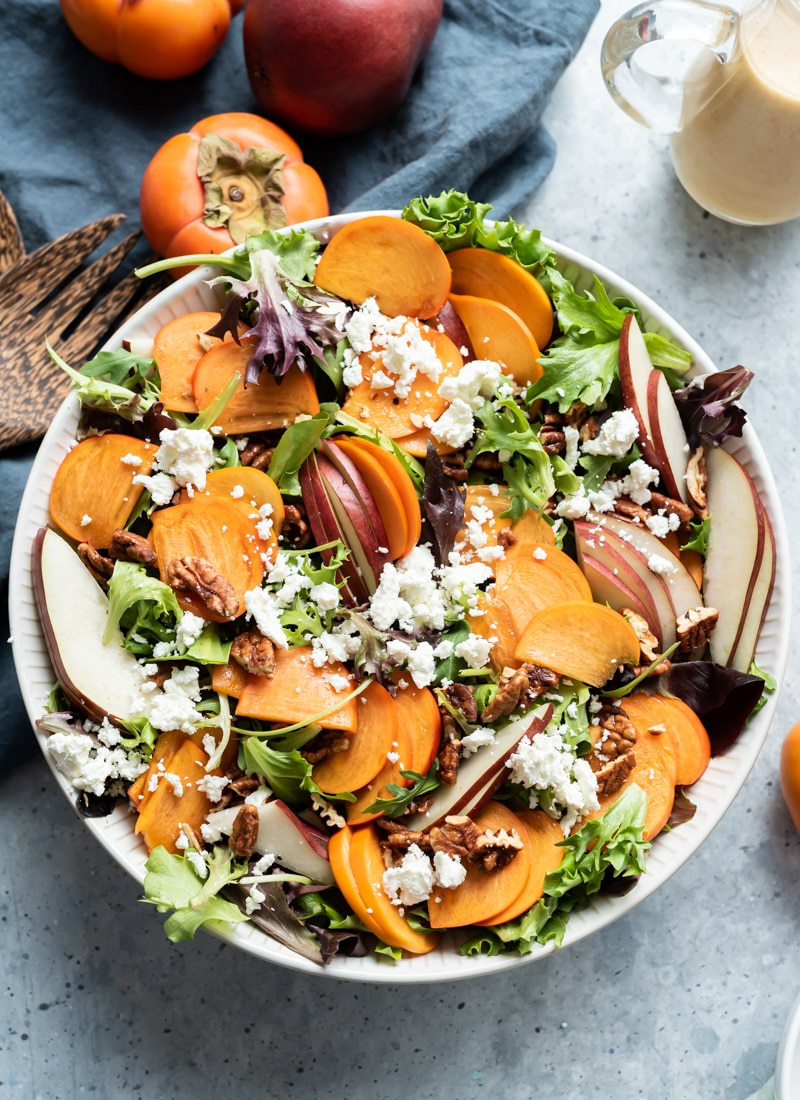 white bowl filled with lettuce, persimmon slices, pear slices, pecans, goat cheese, bottle of vinaigrette