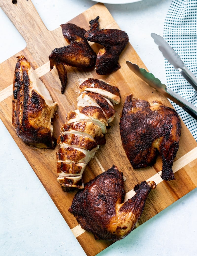 wooden cutting board with handle with various pieces of smoked chicken on it, one piece is sliced, bbq tongs