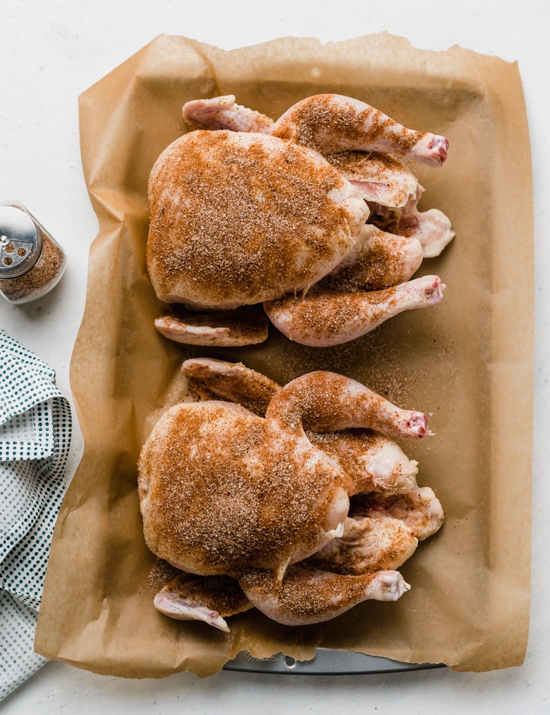 two whole raw chickens covered in spice blend on a baking tray covered with parchment paper