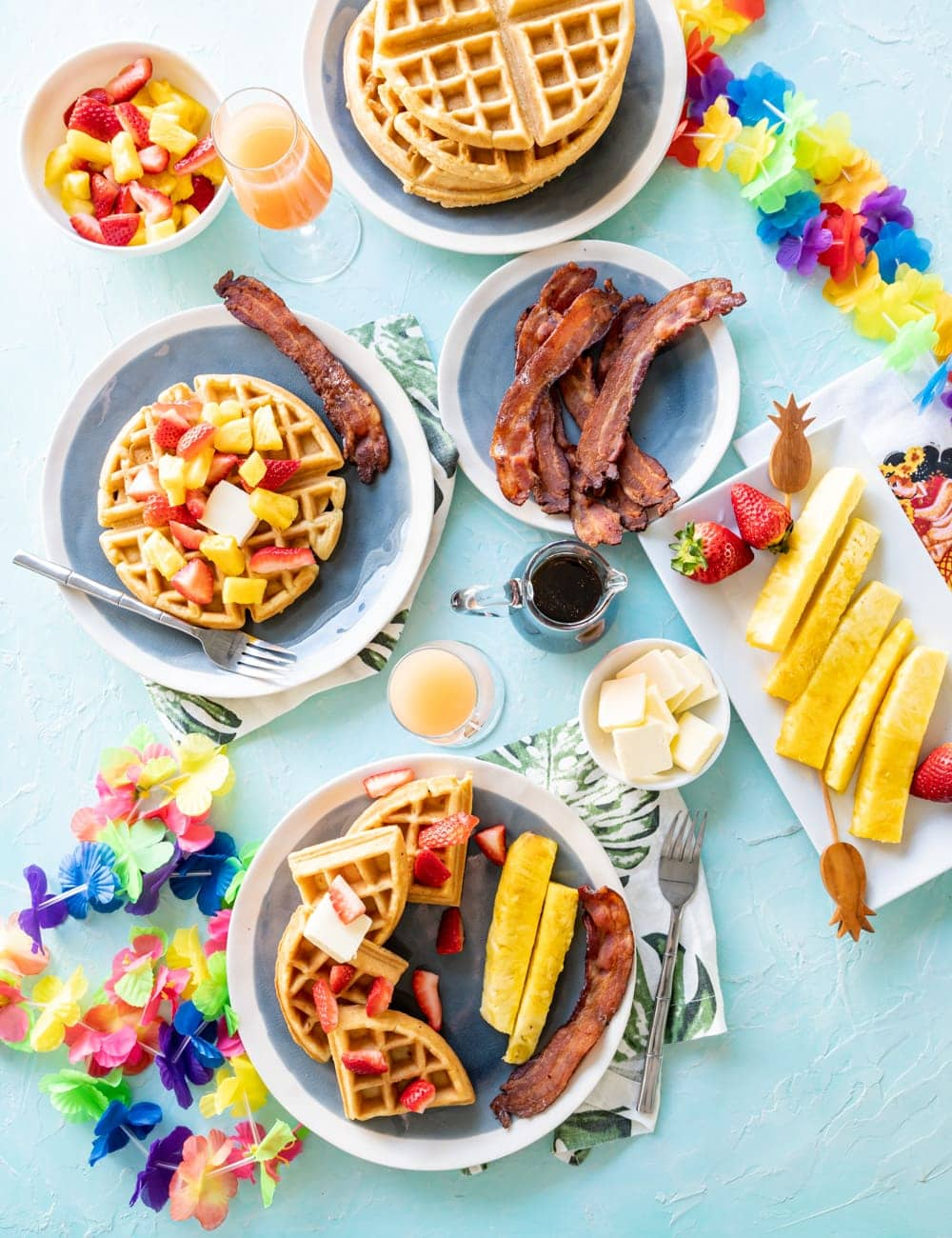 coconut mochi waffles on blue plates with pineapple spears, pieces of cooked bacon, glass with mimosa cocktail in it, glass syrup bottle, rainbow Hawaiian lei on table