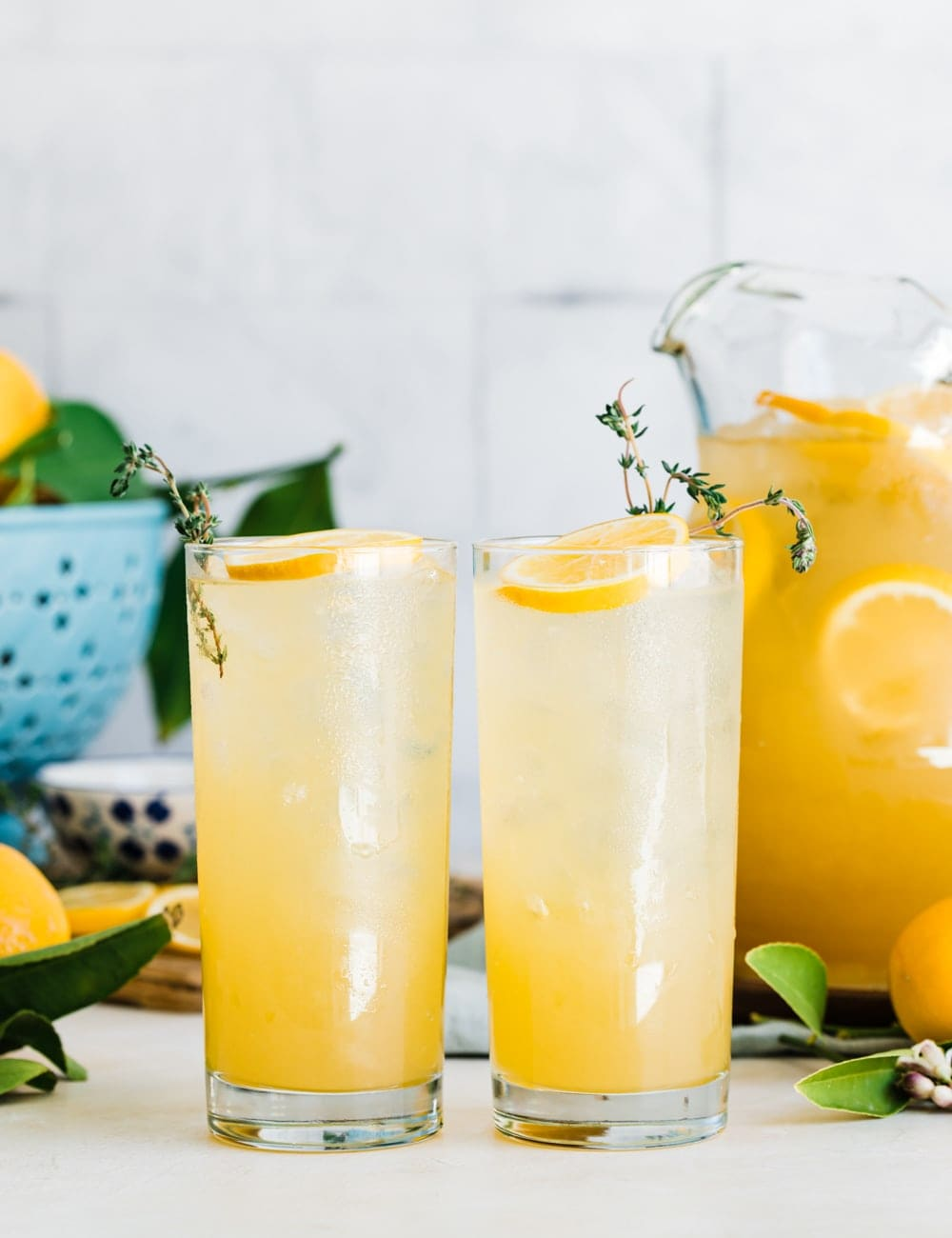 two tall collins glasses filled with lemonade, lemon slices and fresh thyme in glasses, pitcher or lemonade, fresh whole lemons, blue bowl with lemons, cutting board with lemon slices