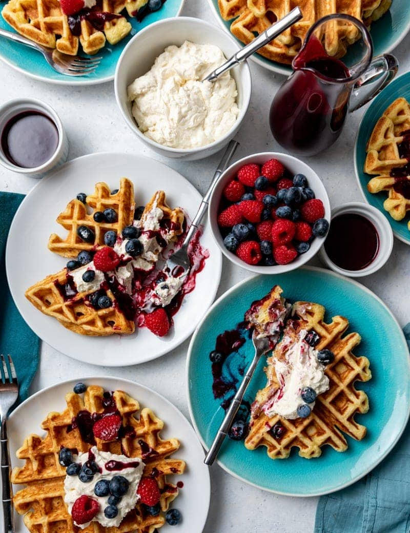 Several white and aqua plates with waffles on each plate, each waffle topped with whipped cream, blueberries and raspberries, dark red syrup, bowl of fresh raspberries and blueberries