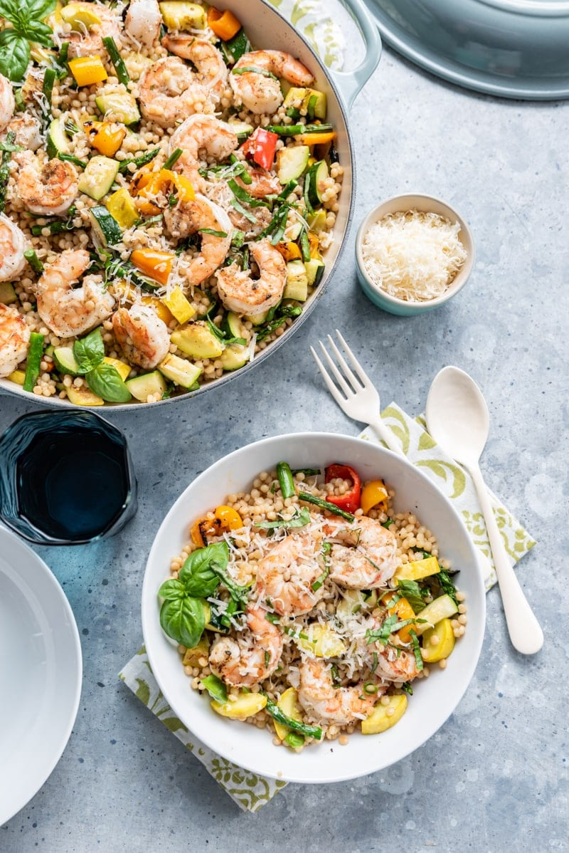 large light blue pan filled with Israeli couscous, cooked shrimp, various squash and peppers, fresh basil, shredded parmesan, small white bowl filled with same ingredients, green and white napkin
