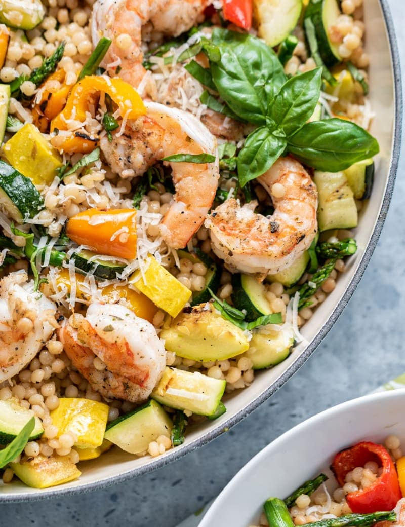 large light blue pan filled with Israeli couscous, cooked shrimp, various squash and peppers, fresh basil, shredded parmesan, metal tongs, green and white napkin