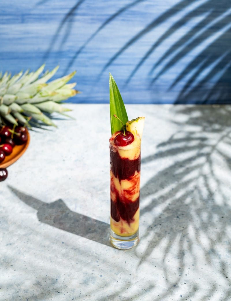 tall skinny glass with alternating layers of yellow and red frozen cocktail, cherries, palm leaf shadow