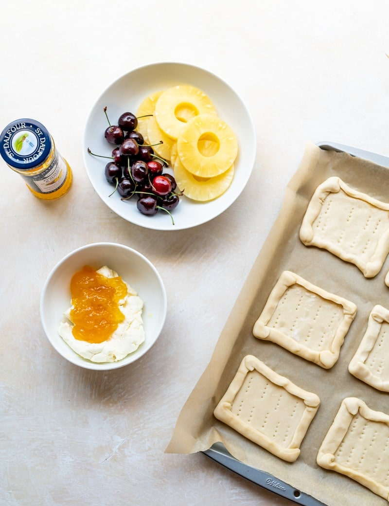 Prep photo for pineapple tarts, cream cheese and jam in small white bowl, cherries and pineapple rings in small white plate, jar of jam, beige background