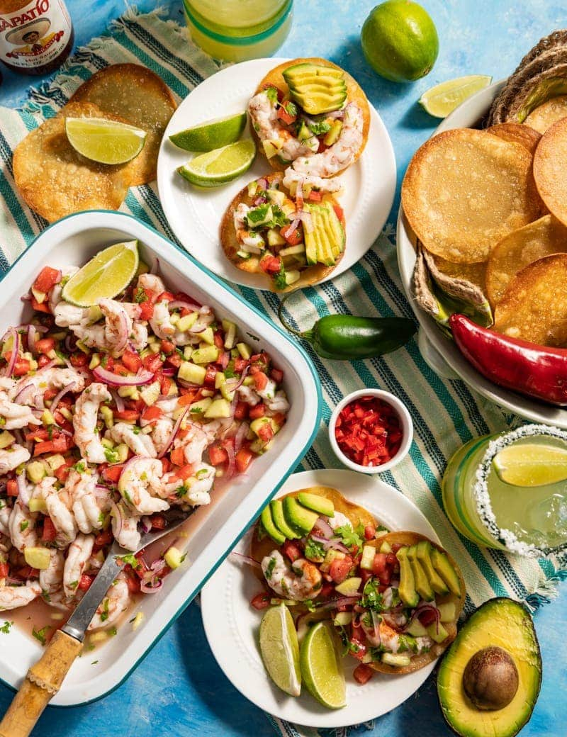 Beautiful food photography of Mini Shrimp Ceviche Tostada recipe with tray of shrimp ceviche, margaritas, lime slices, diced chilies in small bowls basket of round chips small plates with servings of ceviche
