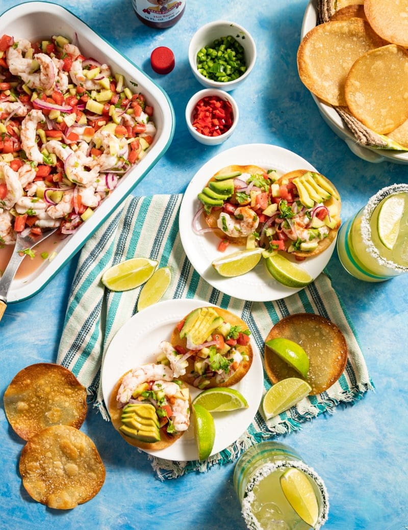 two small white plates with mini shrimp ceviche tostadas on them with lime slices, tray of shrimp ceviche, margaritas diced chilies in small bowls basket of round chips
