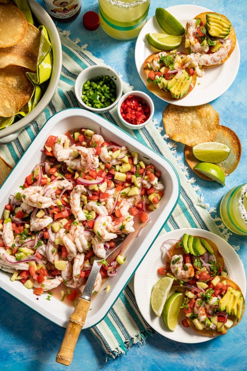Beautiful food photography of Mini Shrimp Ceviche Tostada recipe with tray of shrimp ceviche, small plates with mini tostadas, margaritas, bowl of chips, bowls of sliced chilies