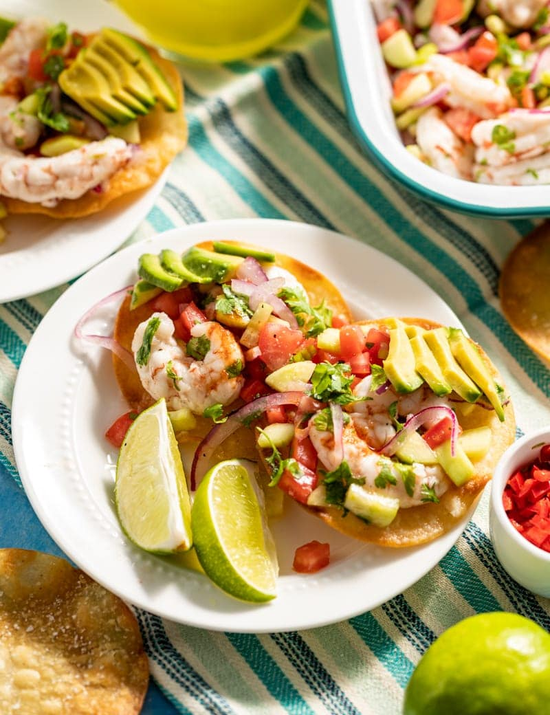 close up of small plate of mini shrimp ceviche tostadas on blue striped napkin in background