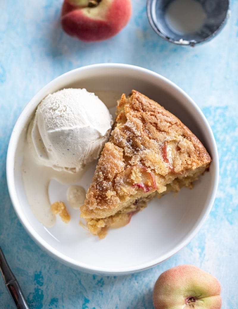 overhead close up of Summertime Brown Sugar White Peach Buttermilk Cake slice in bowl with ice cream www.pineappleandcoconut.com