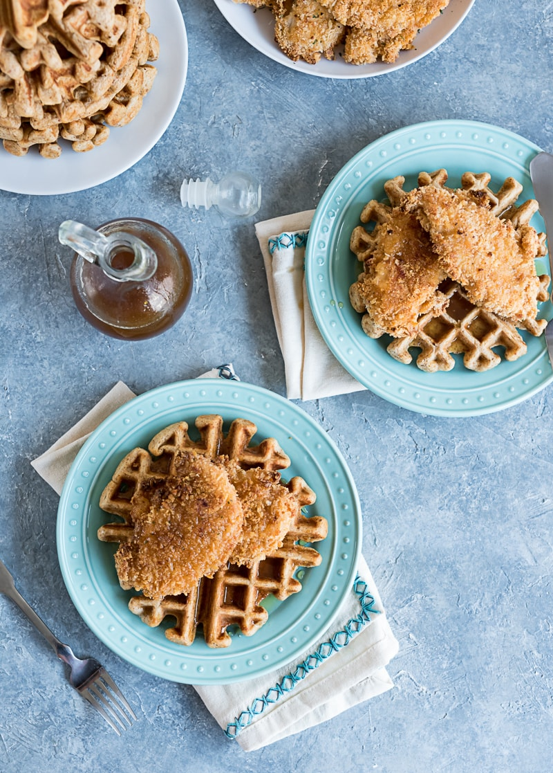 overhead image looking down ontwo aqua plates with one waffle and two breaded baked chicken pieces on each waffle, glass syrup bottle, white napkins with aqua stitching,
