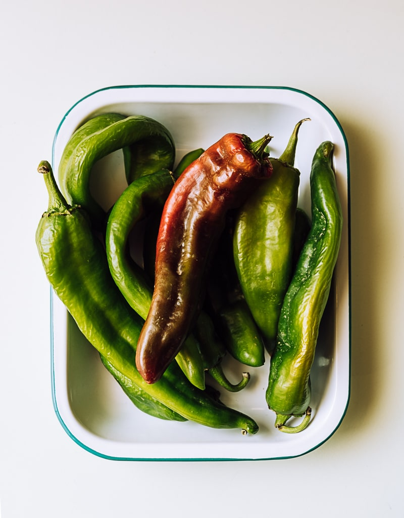 green and red hatch chilis in a white pan