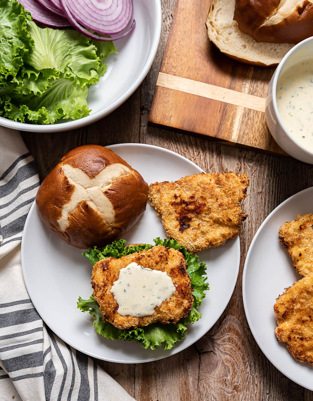white plate with open faced sandwich , breaded fried chick on top of lettuce, white mayonnaise sauce, red onion rings, plate with thin fried chicken, bottle and glass of beer, bowl with lettuce and onions, cutting board with pretzel buns and bowl of mayonnaise sauce