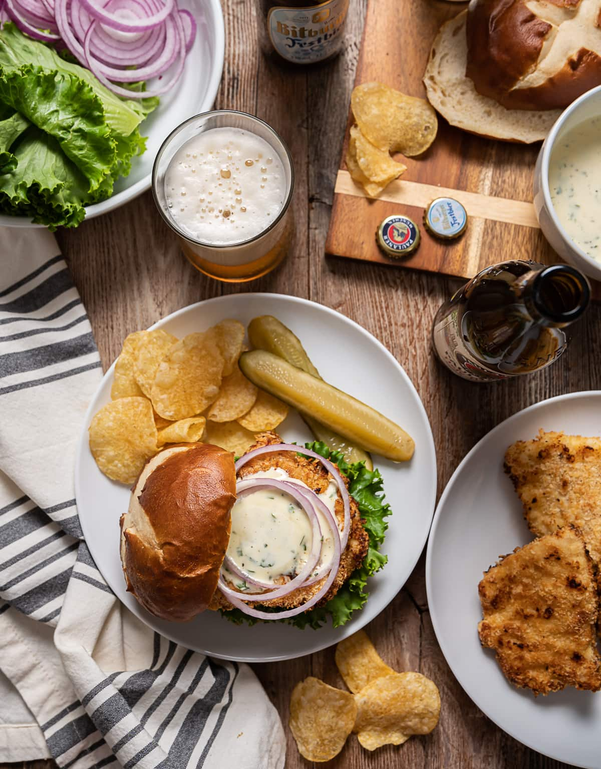 chicken schnitzel sandwich with mayonnaise sauce, red onion rings, plate with thin fried chicken, bottle and glass of beer, bowl with lettuce and onions, cutting board with pretzel buns and bowl of mayonnaise sauce.