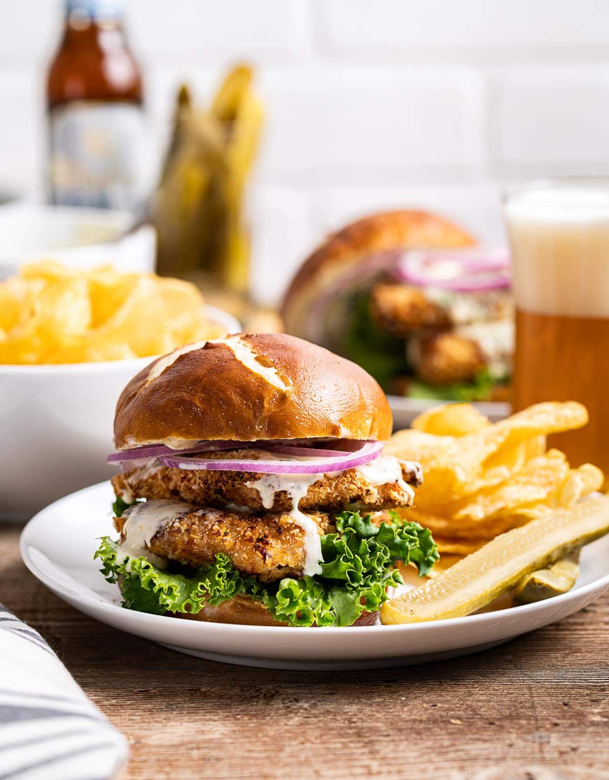 air fryer chicken sandwich with green lettuce, red onion slices, pickles and chips on plate, beer