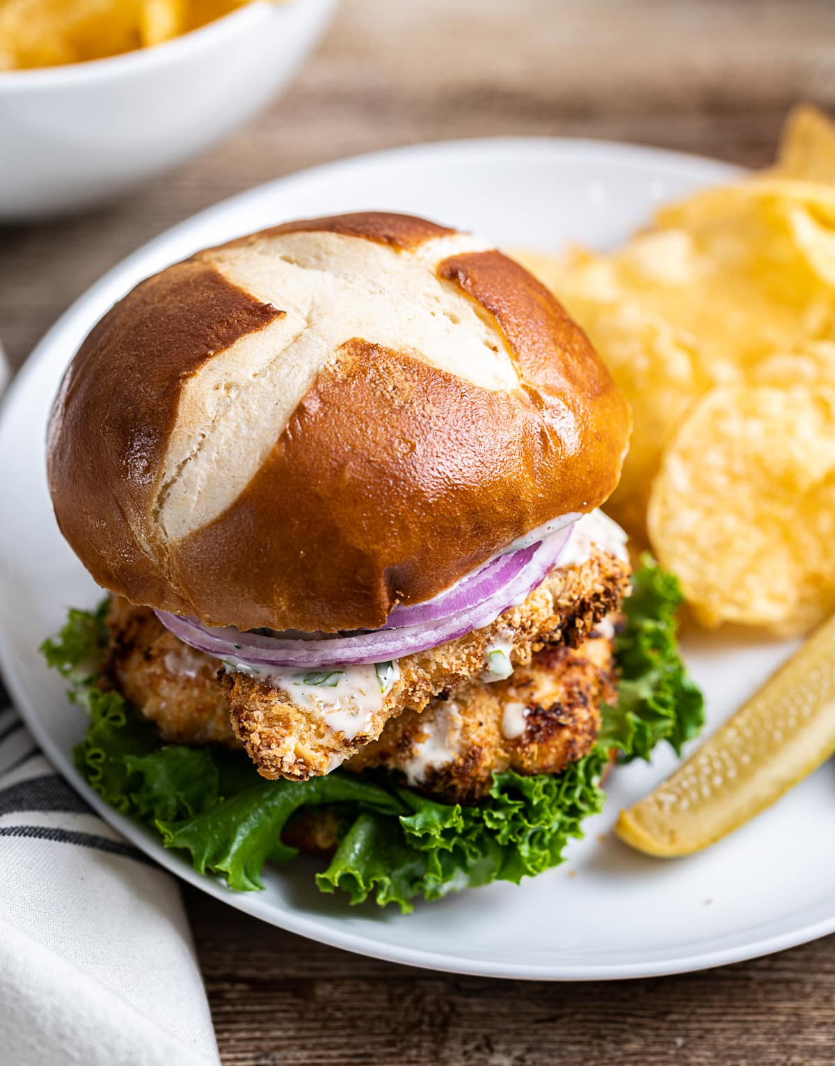 chicken schnitzel sandwich on a white plate with potato chips and pickle