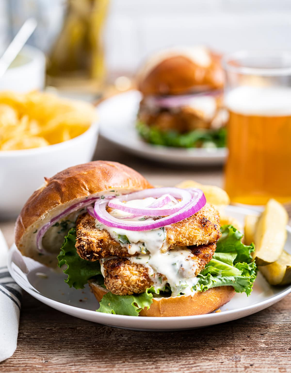 two pieces of breaded air fryer chicken sandwiched in a pretzle bun with green lettuce, red onion slices, pickles and chips on plate, bowl of chips, glass and bottle of beer