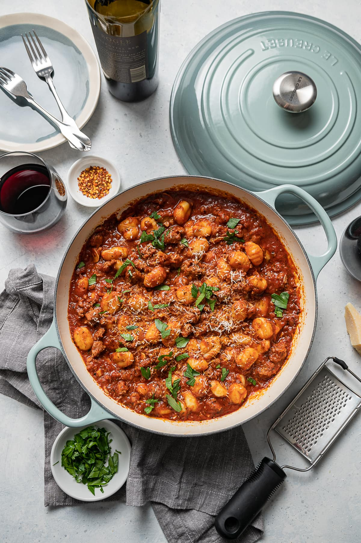 large aqua pan with sausage and gnocchi with red tomato sauce, glasses of red wine, bowl of green parsley, bowl of red pepper flakes, plates, forks, bottle of wine