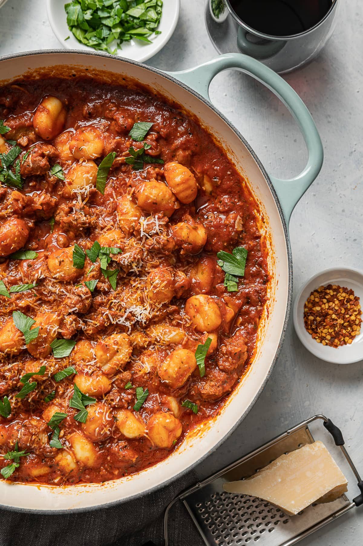 large aqua pan with sausage and gnocchi with red tomato sauce, glasse of red wine, bowl of green parsley, bowl of red pepper flakes, grater and chunk of parmesan cheese