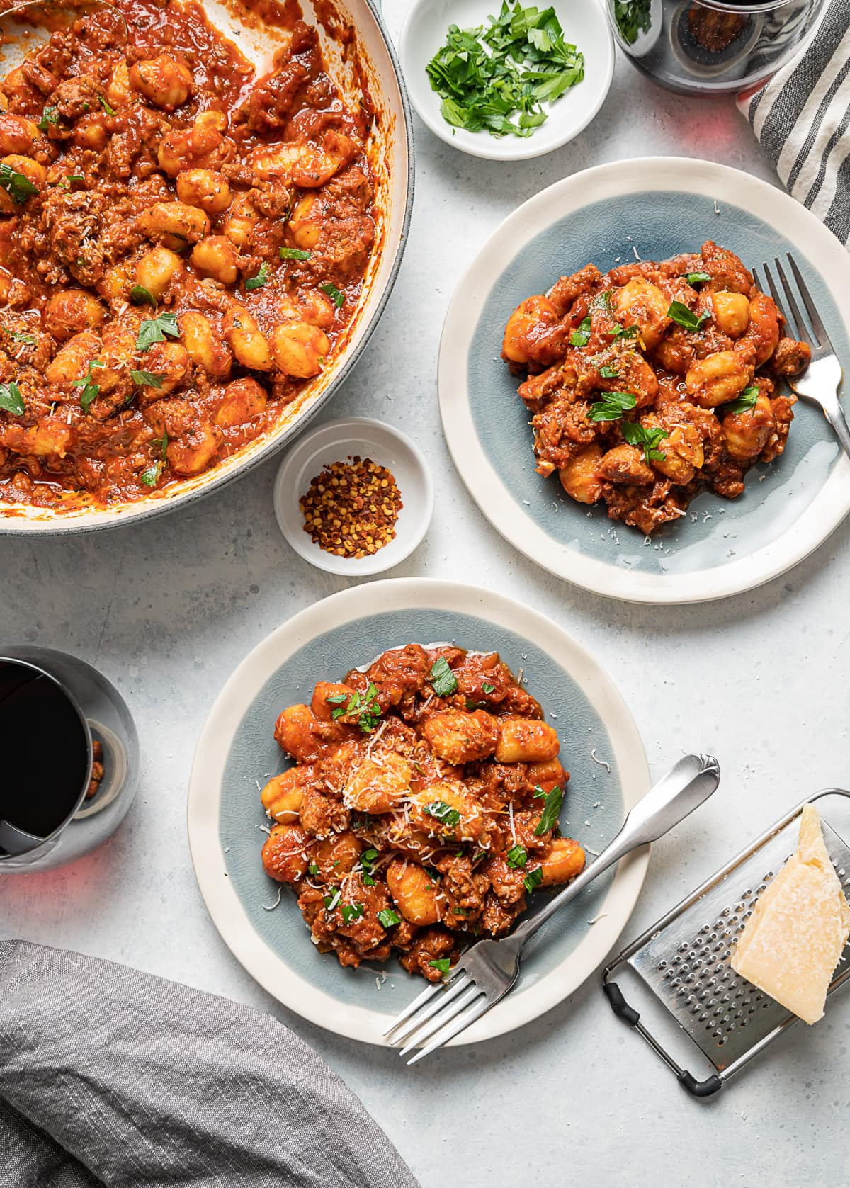 two small plates with red tomato sauce sausage and gnocchi, forks, glasses of wine, small bowls of red pepper flakes and fresh parsley, large bowl of red sauce with sausage and gnocchi
