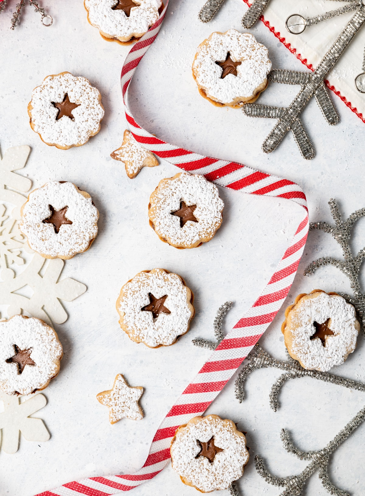 chocolate filled sandwich cookies on a white surface with red and white striped ribbon and silver snowflakes