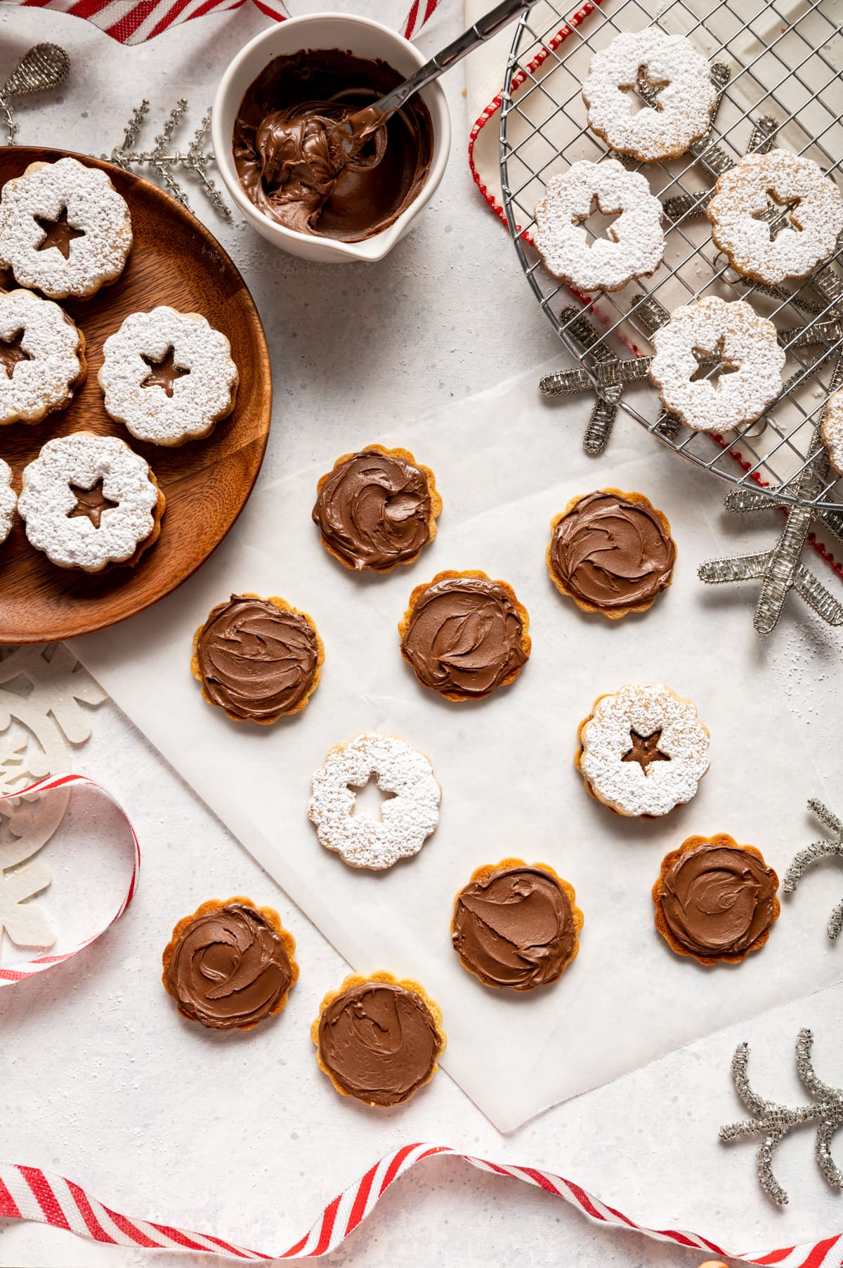 cookies with swirls of chocolate spread on them, chocolate filled sandwich cookies on a wood plate red and white ribbon