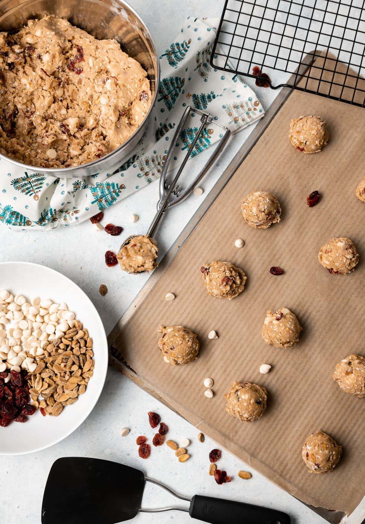oatmeal cookie dough on a tray some dough in a stainless bowl some dough in a cookie scoop bowl of white chocolate chips cranberries and pistachios