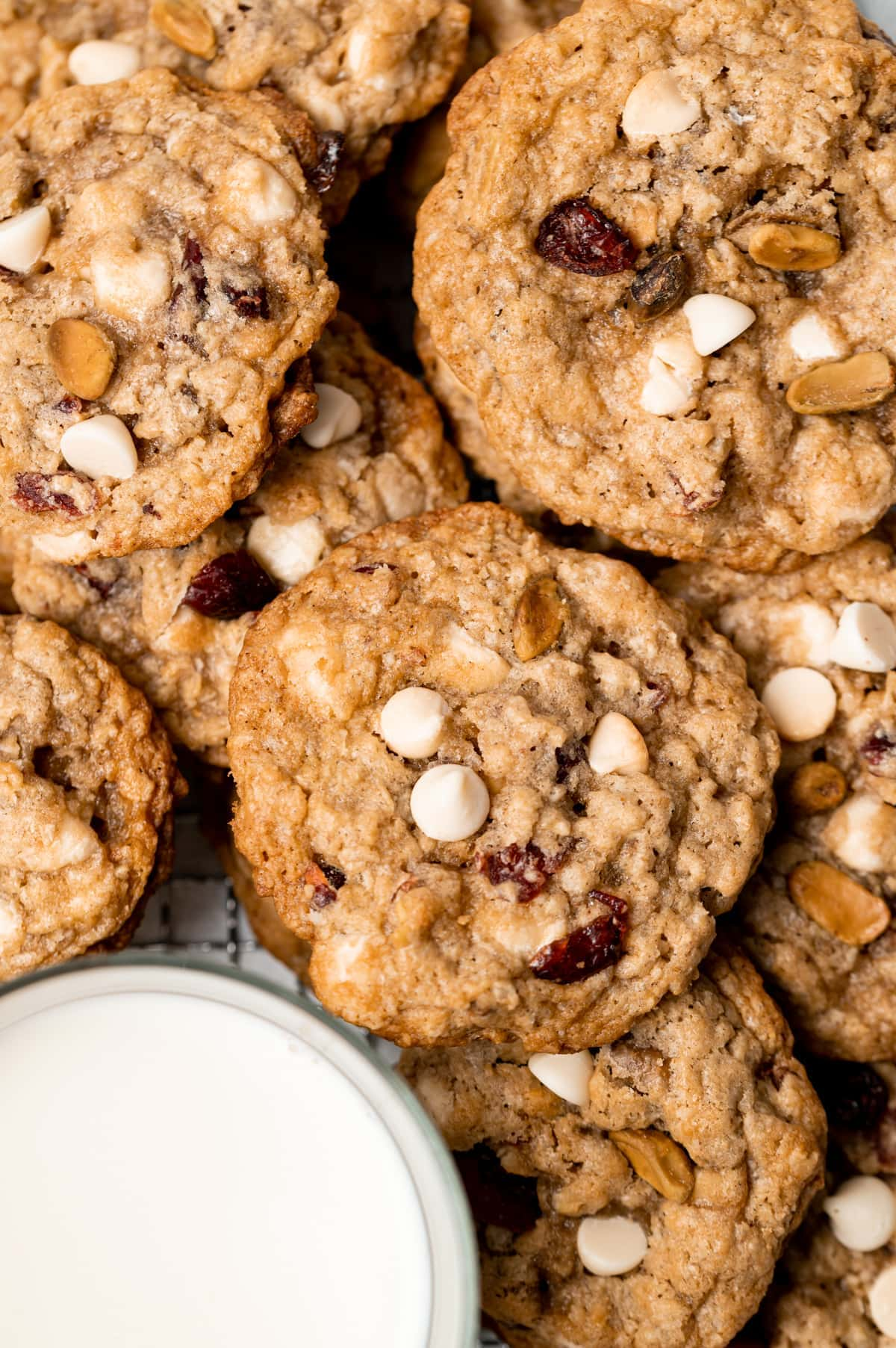 pile of oatmeal cookies with cranberries white chocolate chips and pistachios glass of milk