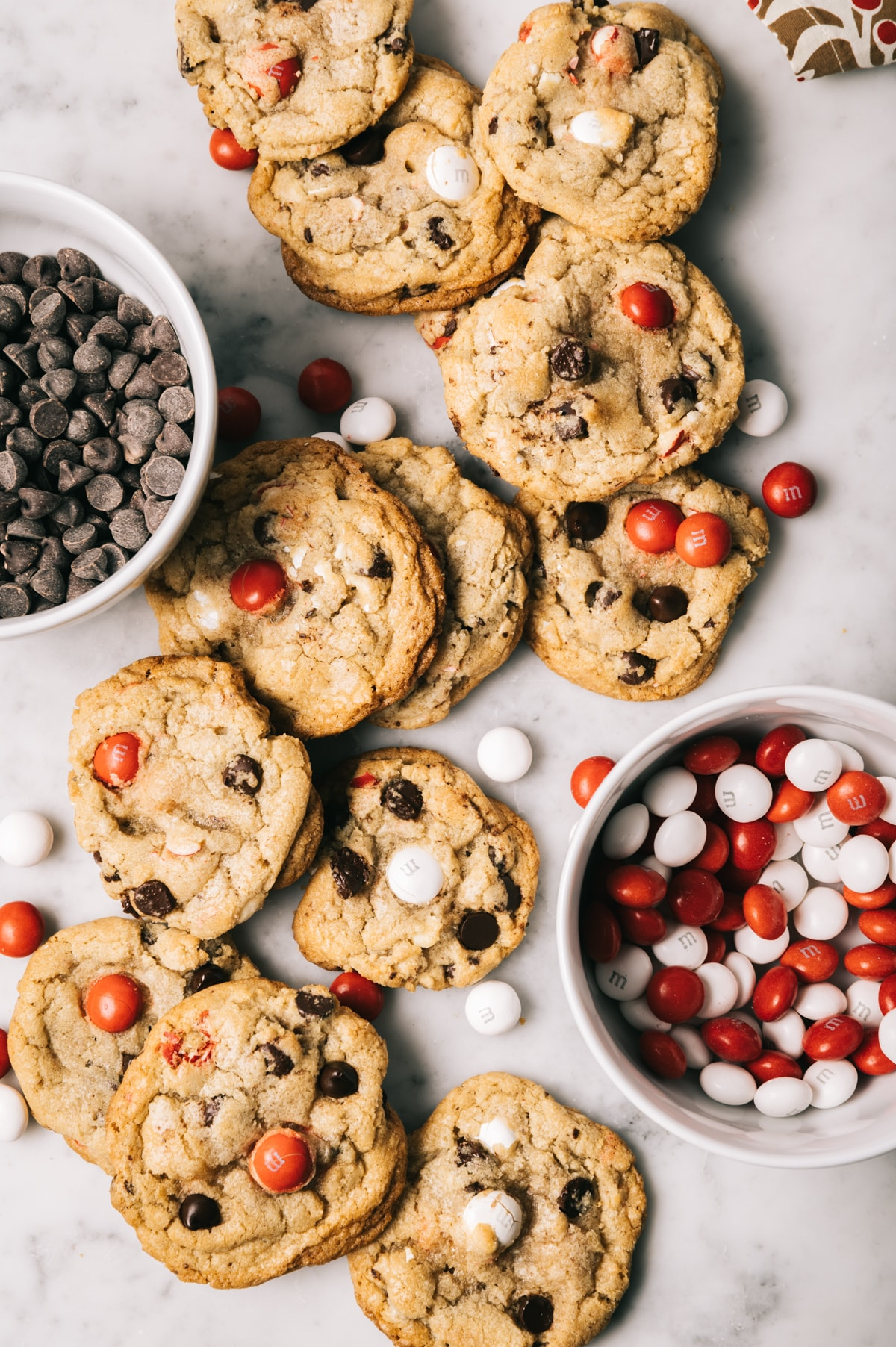 chocolate chip cookies with red and white M&Ms bowl of chocolate chips bowl of red and white M&Ms