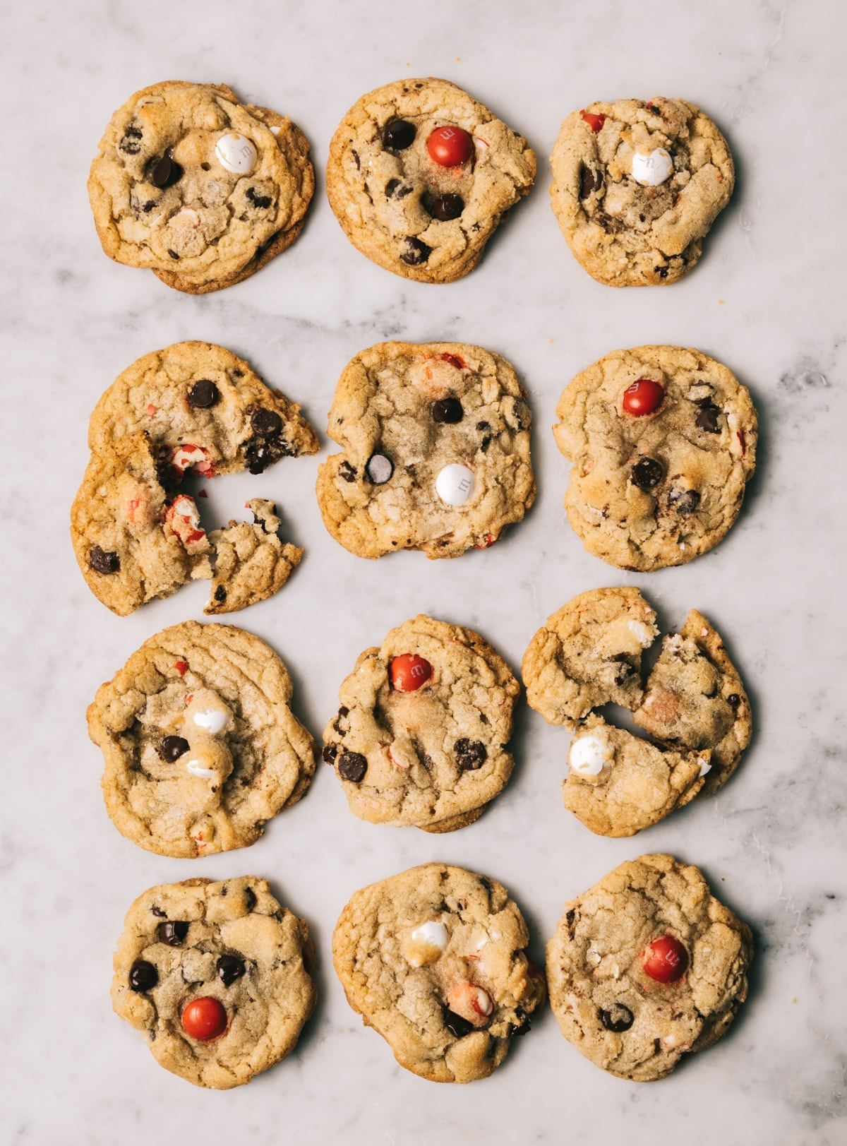 chocolate chip cookies with red and white M&M candies on a white marble surface