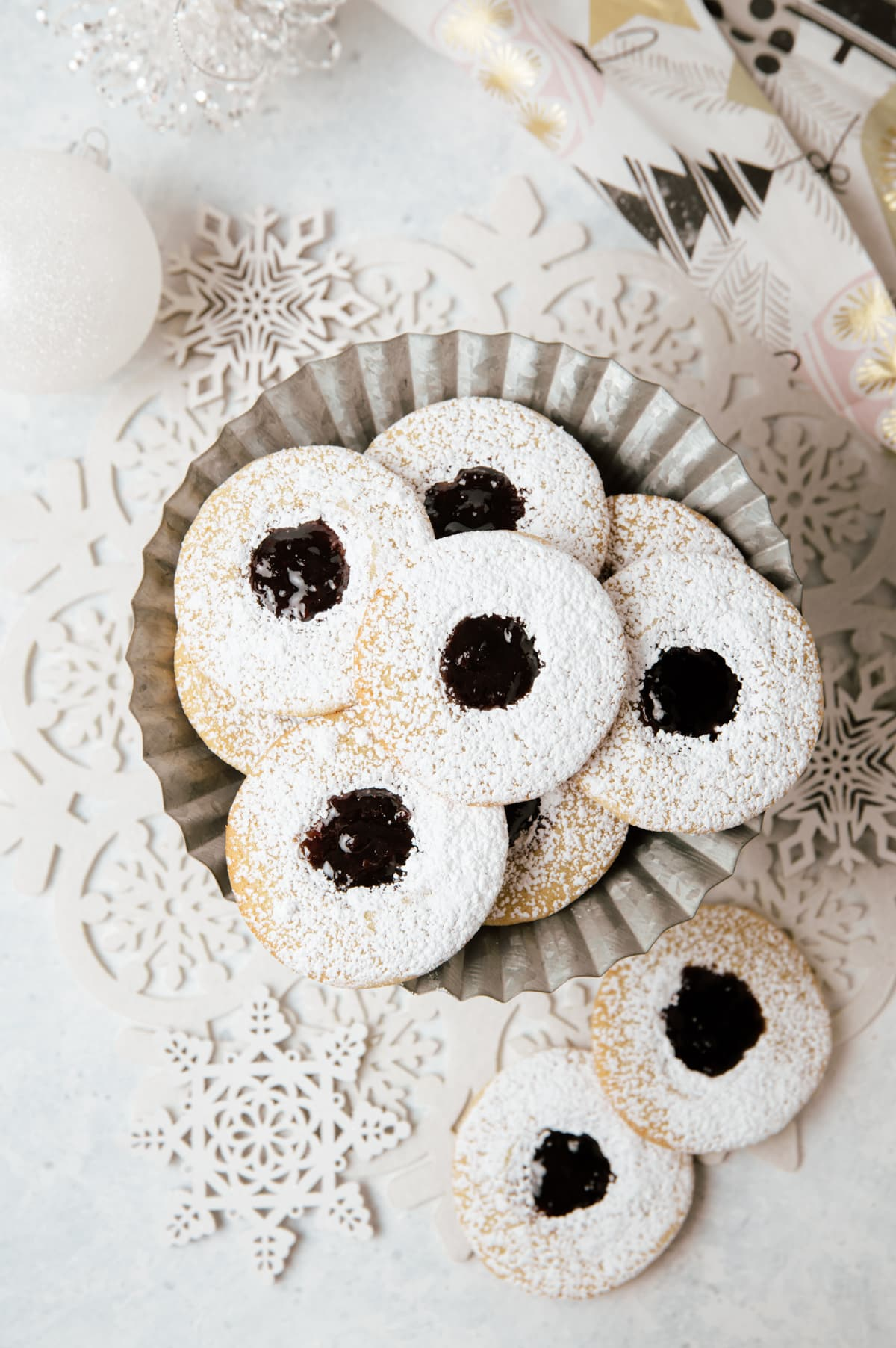 round sandwich cookies with dark purple jam layered on a metal cake plate