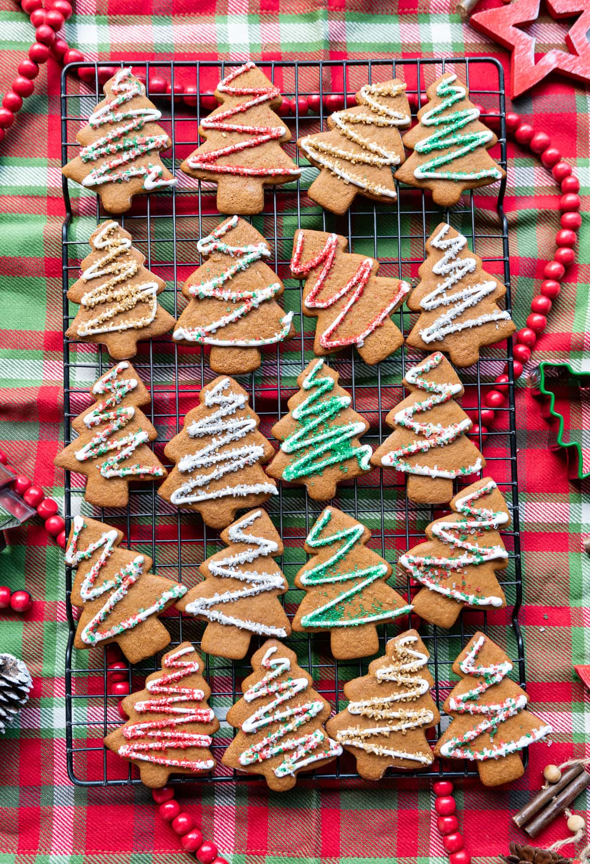 iced gingerbread christmas tree cookies on a wire rack on a red green and white plaid napkin