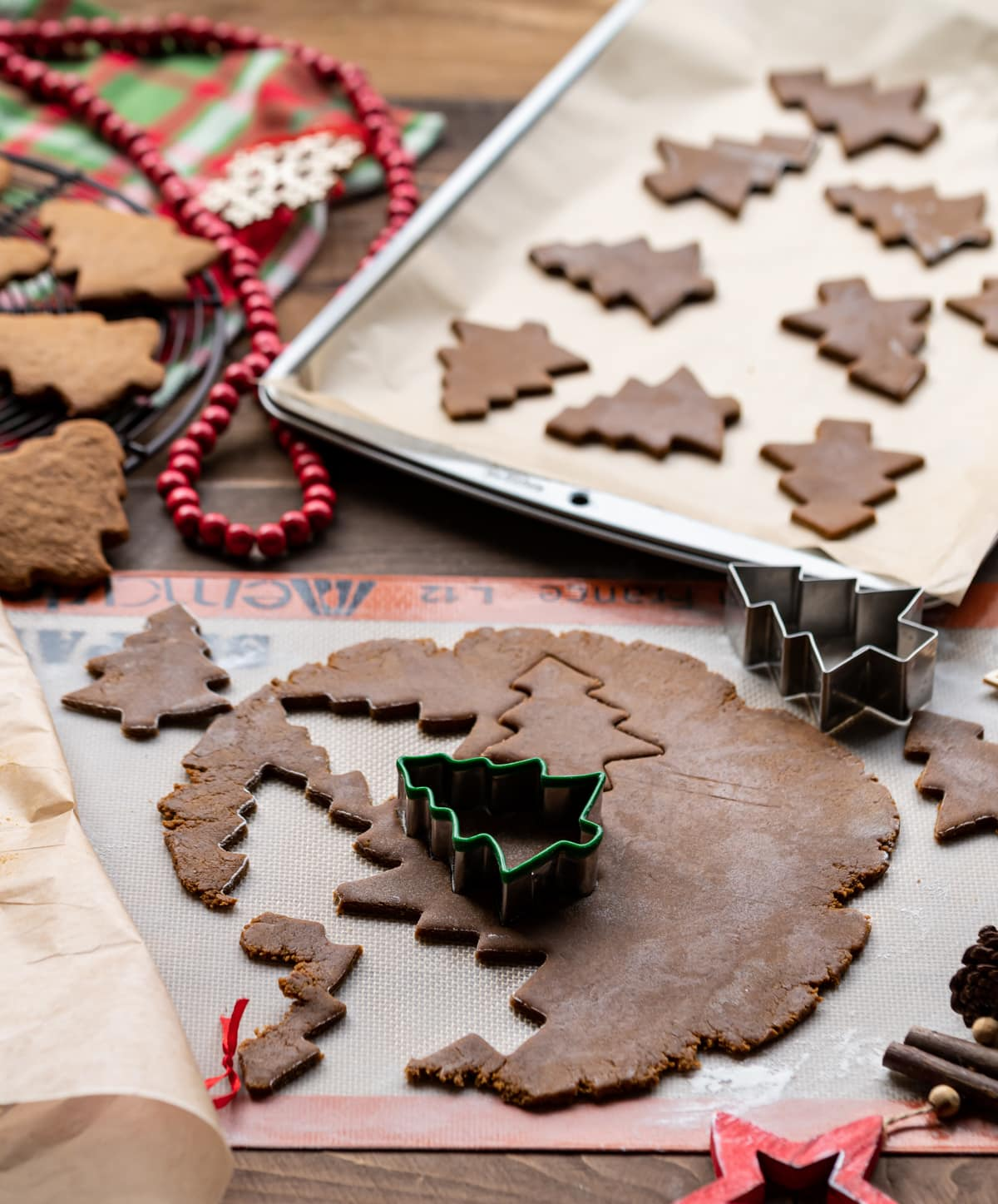 gingerbread cookie dough with Christmas tree shaped cookie cutter, cut out cookies on a baking tray