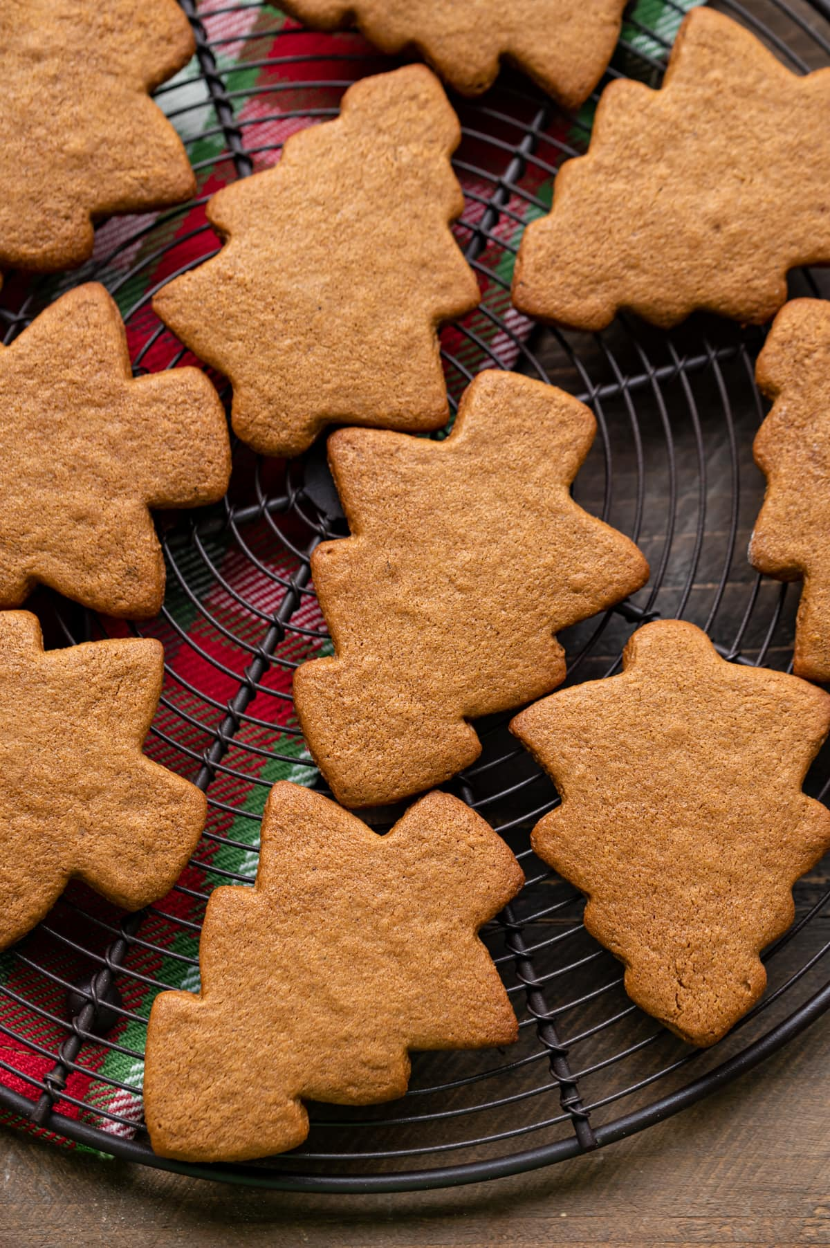 baked gingerbread christmas tree cookies on a round wire cooling rack