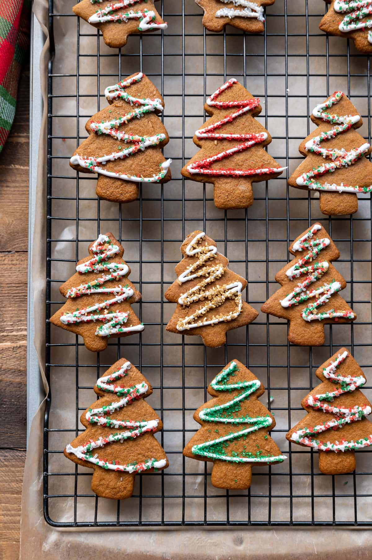 gingerbread cut out cookies on a wire rack with icing and colored sugar