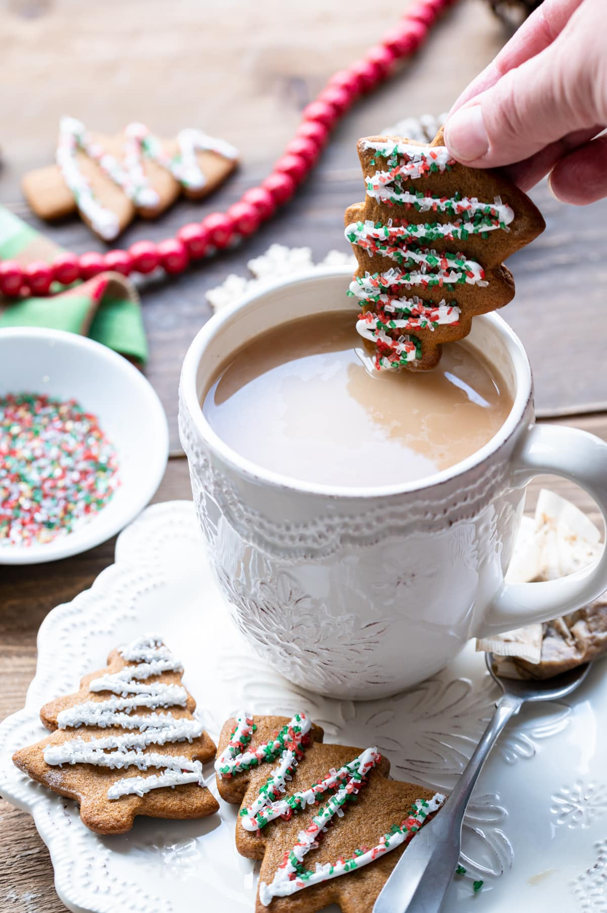 gingerbread christmas tree cut out cookie being dipped into a cup of tea