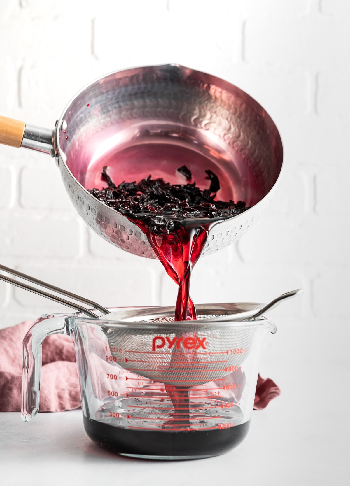 dark red hibiscus syrup in a pan being strained into a large glass measuring cup