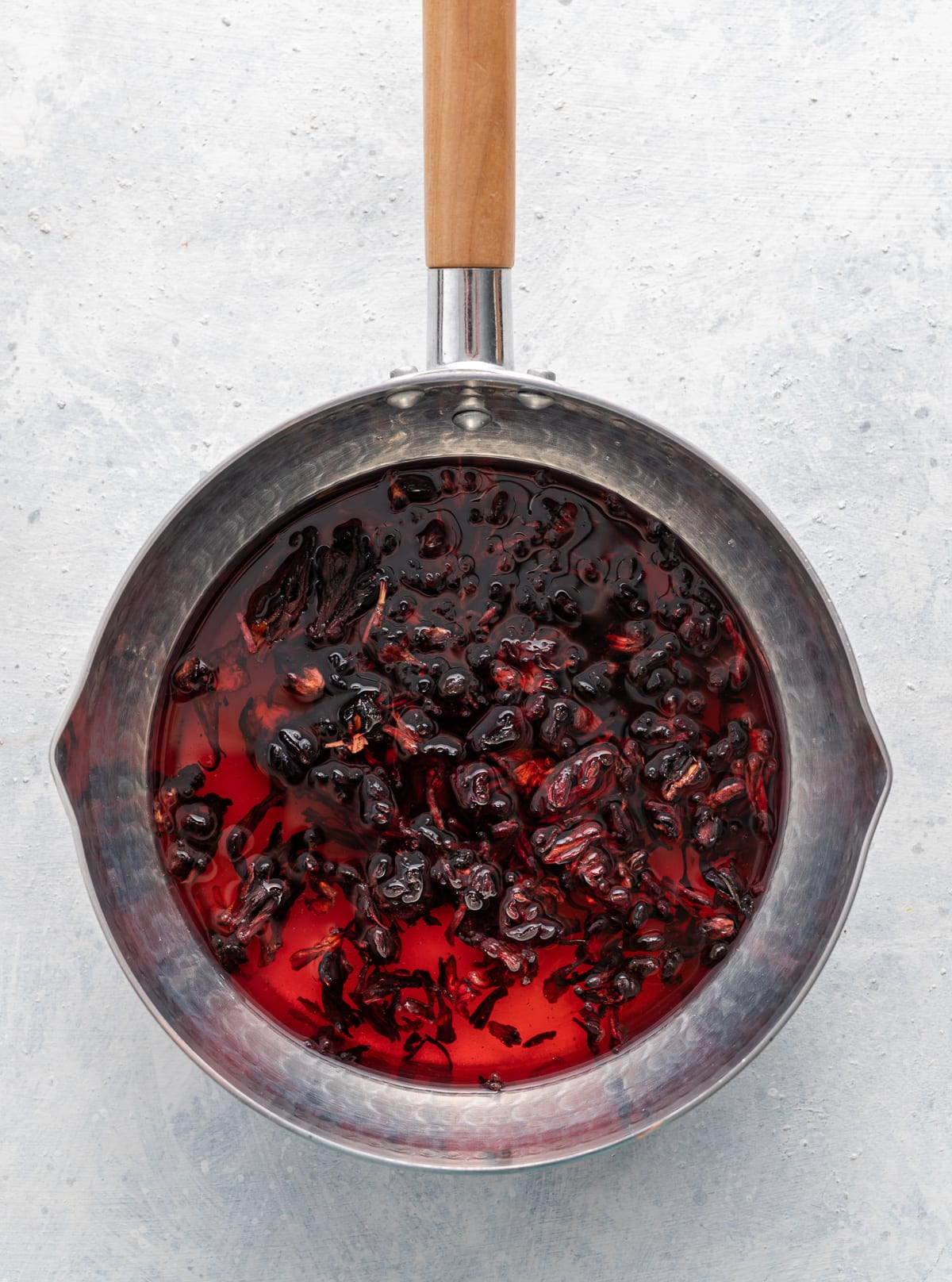 dark red hibiscus syrup in a pan