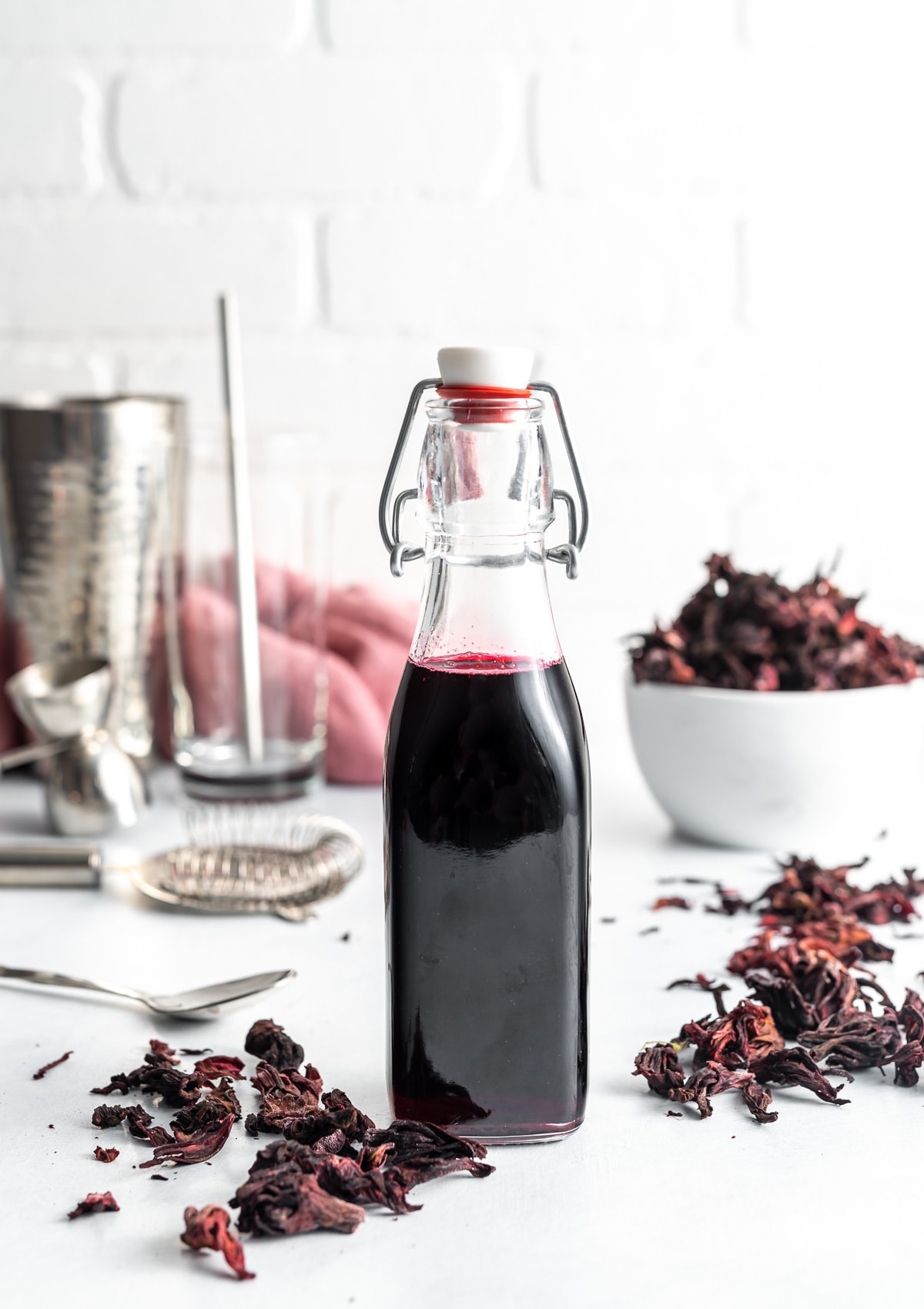 dark red hibiscus syrup in a bottle, dried hibiscus flowers