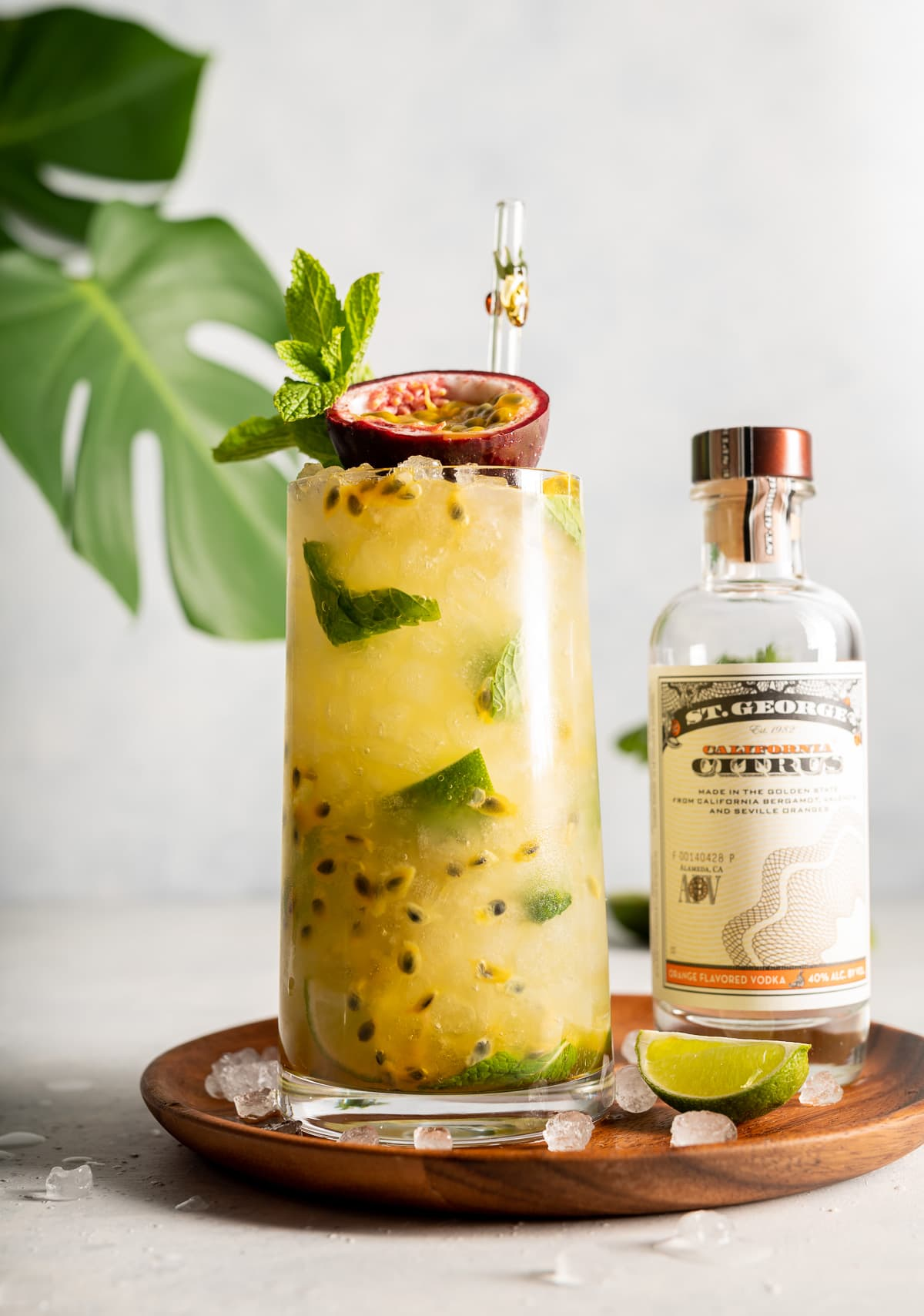 yellow cocktail with green mint and limes passion fruit and green monstera leaves bottle of vodka