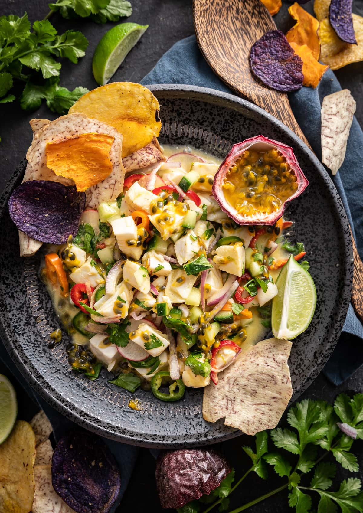 halibut passion fruit ceviche in a black bowl with fresh passion fruit and vegetable chips