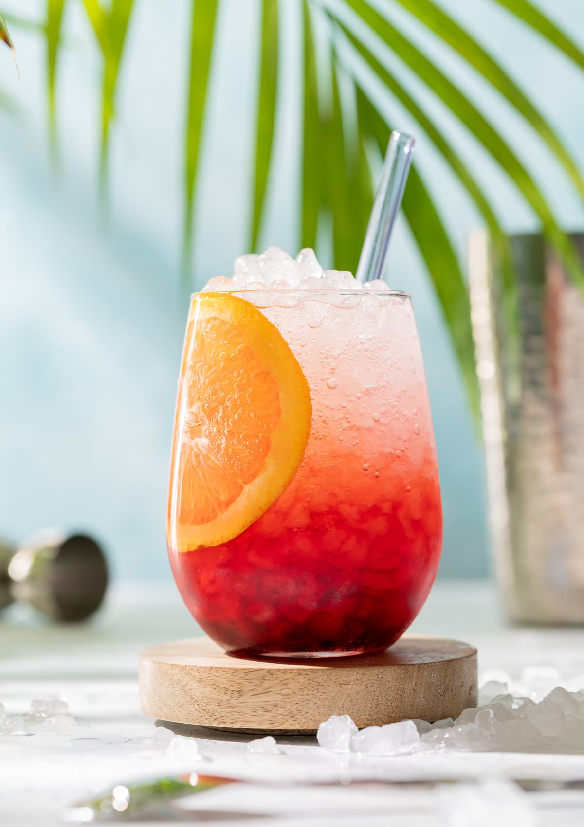 hibiscus spritz red and white cocktail with orange slice yellow plumeria palm leaves