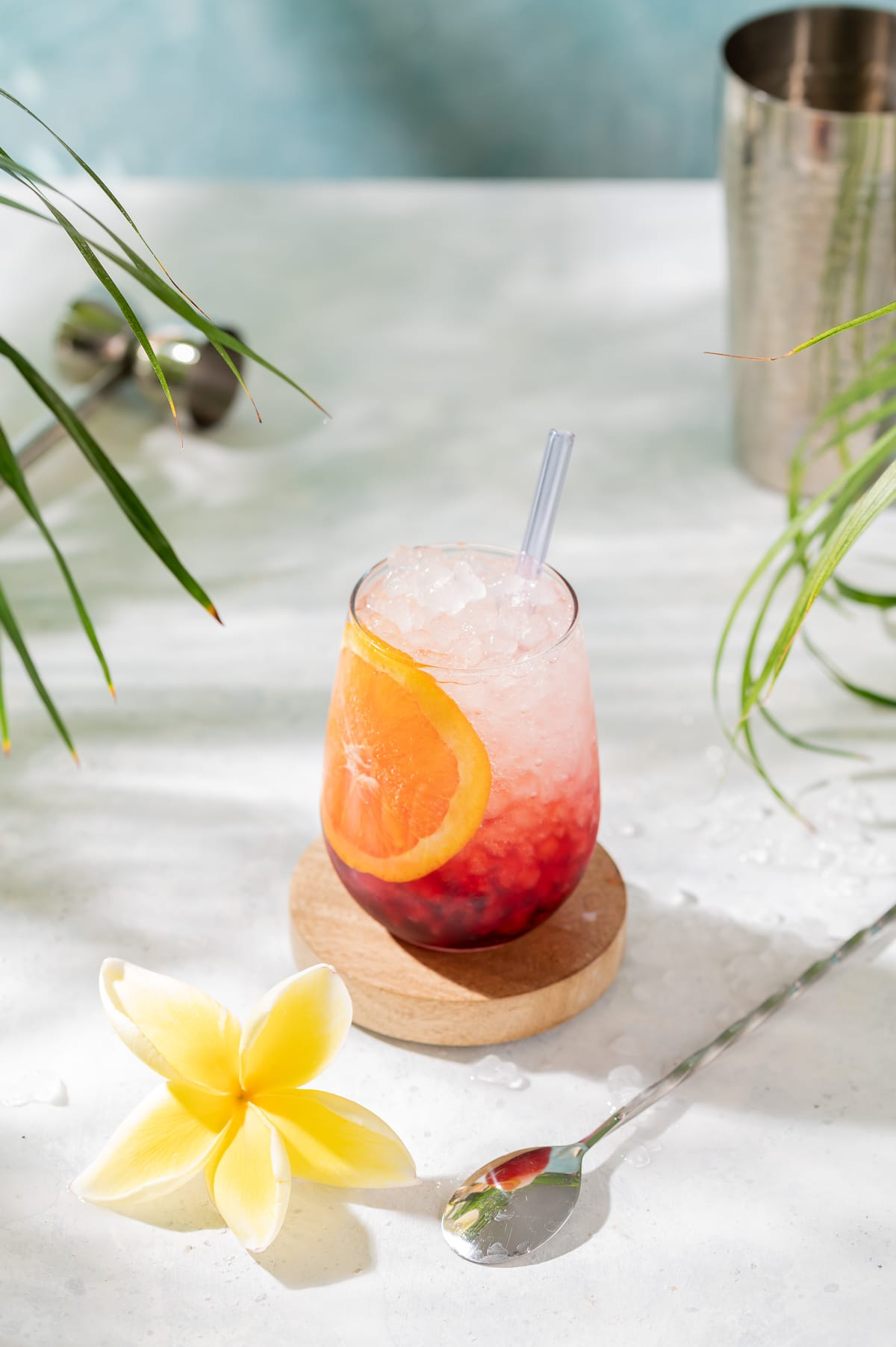 red and white cocktail with orange slice yellow plumeria palm leaves