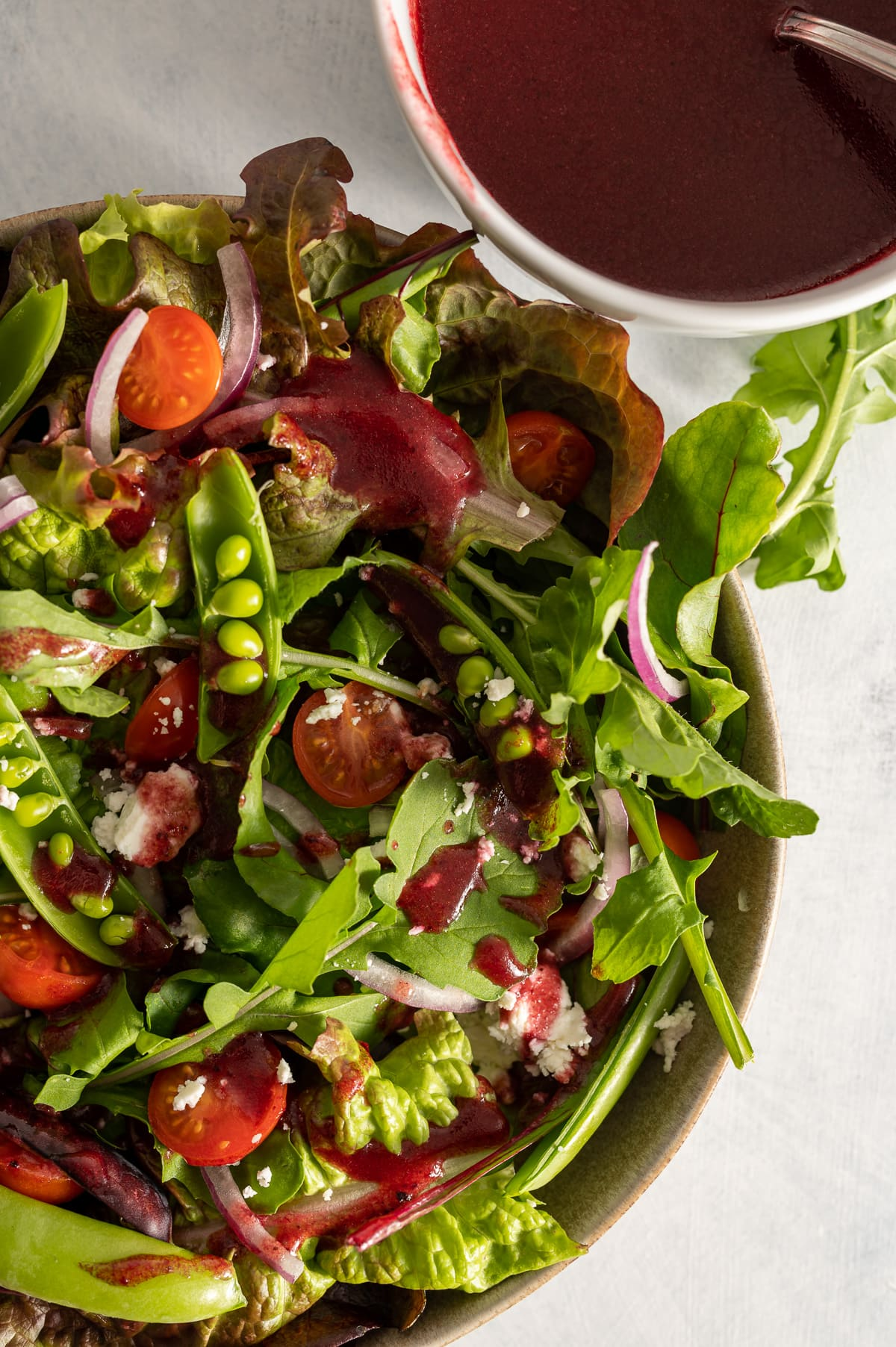 close up of a bowl of salad greens with dark red hibiscus vinaigrette dressing