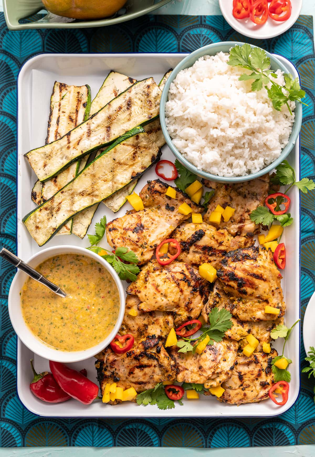 grilled chicken on a tray with mango and red chili slices cilanto pieces bowl of white rice bowl of yellow mango sauce grilled zucchini slices