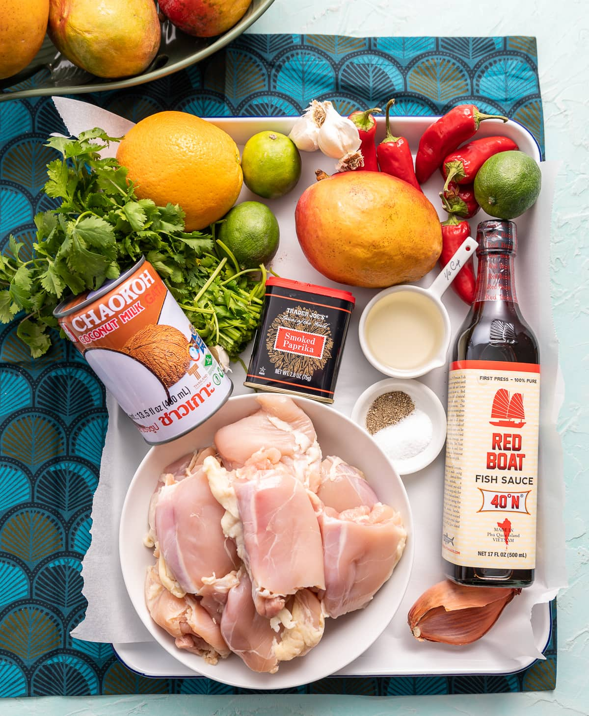 various items on a tray chicken mangoes red peppers limes can of coconut milk garlic bottle of fish sauce shallot