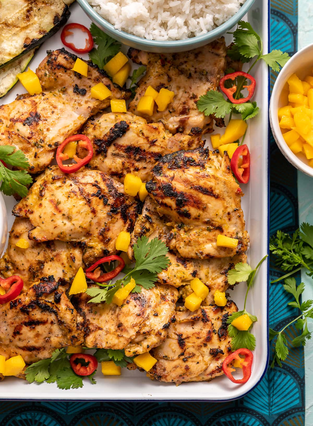 grilled chicken on a tray with mango and red chili slices cilanto pieces
