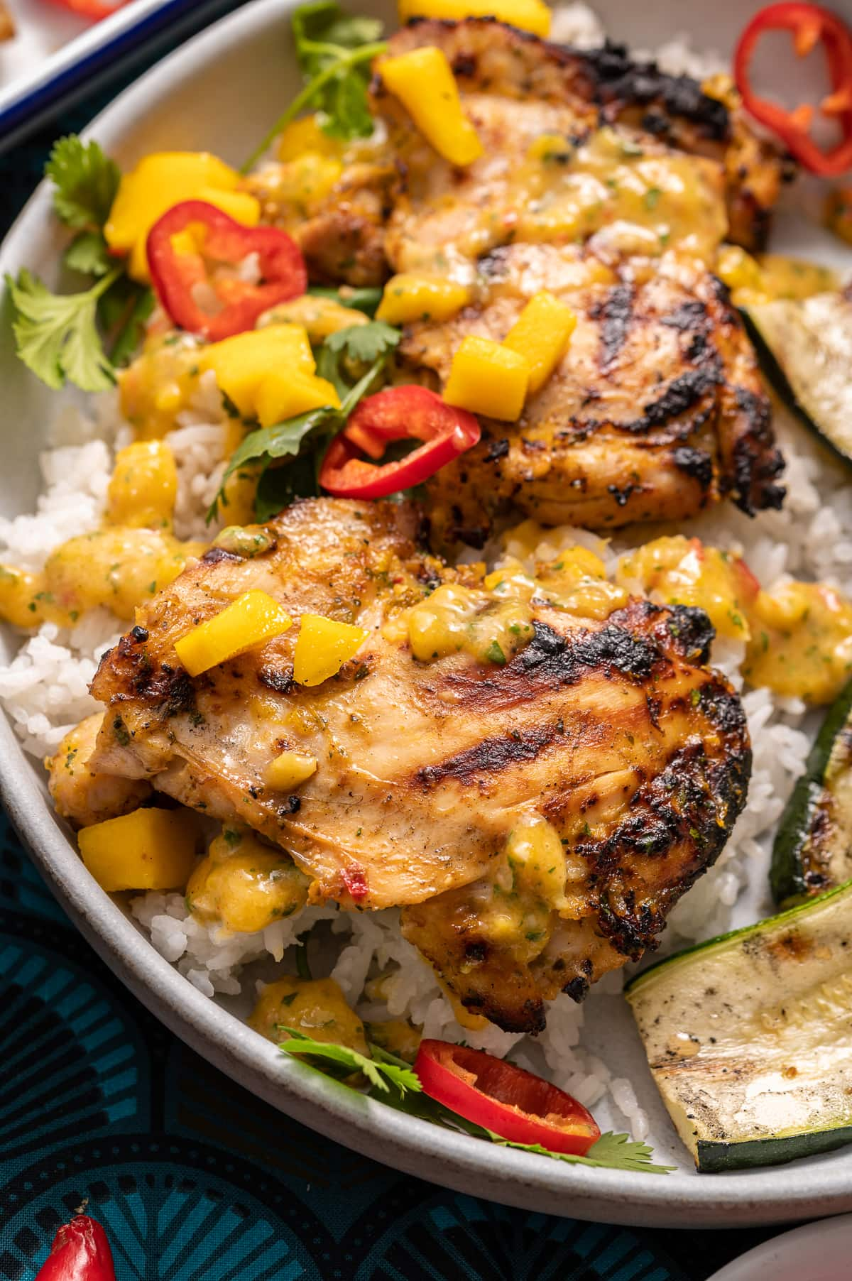 grilled chicken on a plate with mango and red chili slices cilanto pieces grilled zucchini slices